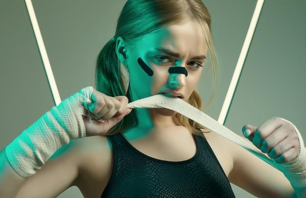 Sterk mooi meisje met blond haar, zelfverzekerde blik, vuisten in beschermende boksbanden