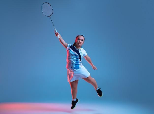 Sterk. mooie dwerg vrouw beoefenen in badminton geïsoleerd op blauwe achtergrond in neonlicht. lifestyle van inclusieve mensen, diversiteit en gelijkheid. sport, activiteit en beweging. kopieerruimte.