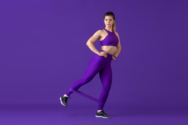 Sterk. mooie jonge vrouwelijke atleet die oefent in, zwart-wit paars portret. sportief kaukasisch fit model met elastieken. body building, gezonde levensstijl, schoonheid en actie concept.