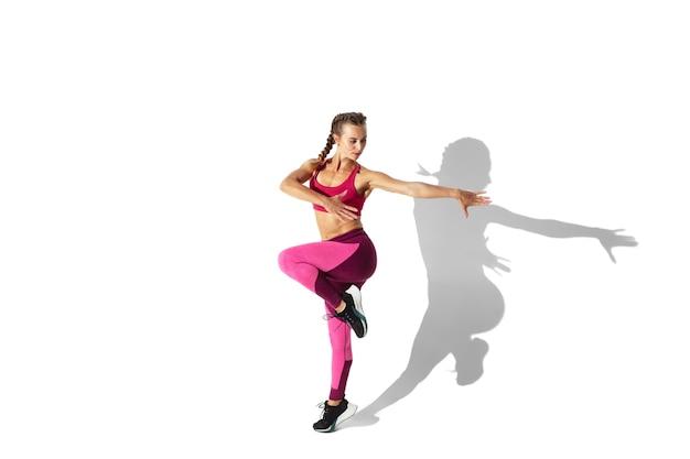 Sterk. mooie jonge vrouwelijke atleet oefenen op witte muur, portret met schaduwen. sportief fit model in beweging en actie. lichaamsbouw, gezonde levensstijl, stijlconcept.
