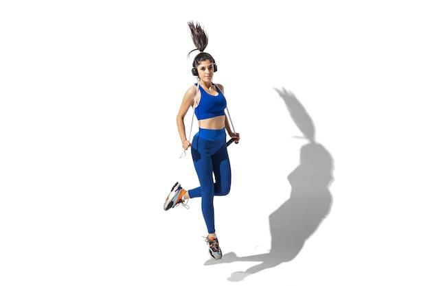 Sterk. mooie jonge vrouwelijke atleet oefenen op witte studio achtergrond, portret met schaduwen. sportief fit model in beweging en actie. lichaamsbouw, gezonde levensstijl, stijlconcept.