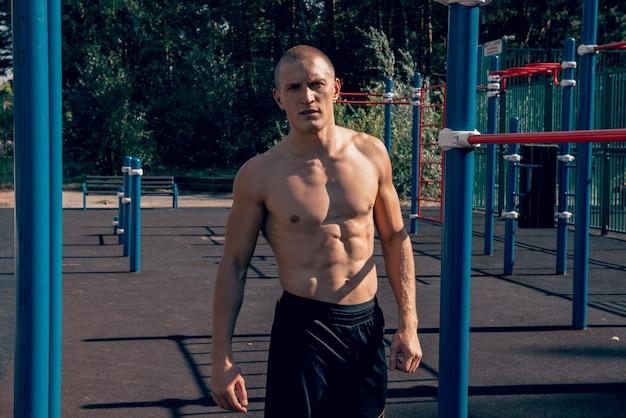 Sterk opgeleide man atleet poseren op het sportveld gespierd sterk lichaam