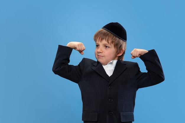 Sterk. portret van een jonge orthodoxe joodse jongen geïsoleerd op blauwe studio muur.