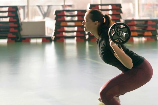 Sterk vrouwgewichtheffen bij de gymnastiek die gelukkig kijkt