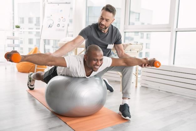 Sterk zijn. vrolijke hardwerkende man die een fysieke oefening doet op de medball terwijl hij zijn spieren ontwikkelt