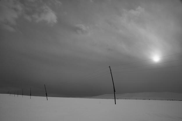 Sterk zwart-wit winterlandschap met wolken en elektrische pilaren