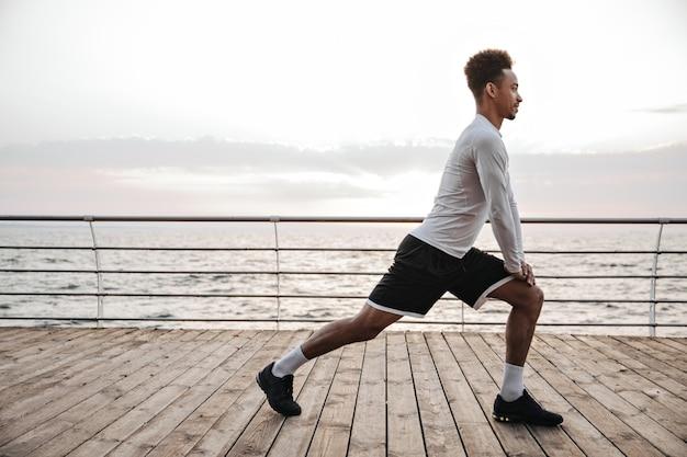 Sterke actieve, krullende man met donkere huid in zwarte korte broek en wit t-shirt met lange mouwen, hurkt, traint en strekt zich uit in de buurt van zee