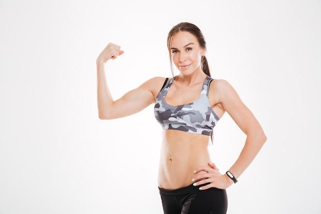 Sterke aërobe vrouw in studio. biceps laten zien. geïsoleerd
