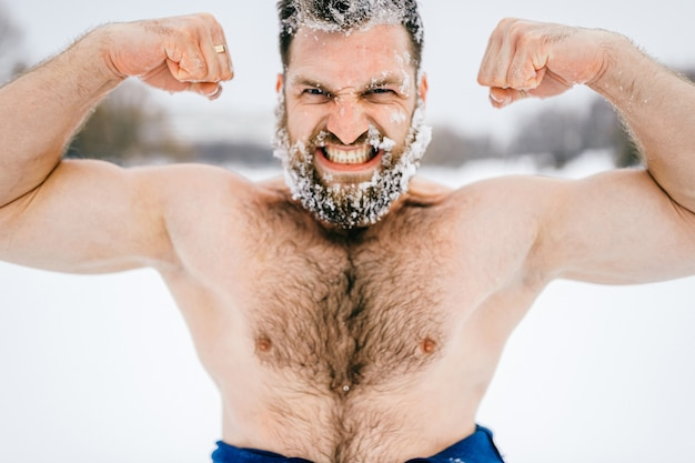 Sterke agressieve brute naakte man met bevroren baard met spieren buitenshuis