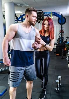 Sterke atleet toont zijn gespierde lichaam aan de mooie vrouw in gezondheidsclub. het glimlachende meisje raakt de bicepsen van het mannetje op de krommingsarm