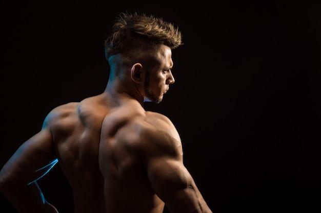 Sterke atletische fitness man die rugspieren, triceps, latissimus op zwarte achtergrond