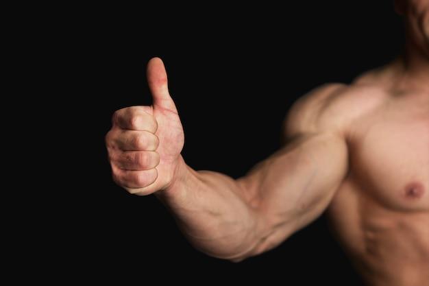 Sterke atletische man met grote duim