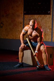 Sterke atletische man poseren met een sporthamer op de achtergrond van de sportschool. een sterke bodybuilder met perfecte buikspieren, schouders, biceps, triceps en borst.