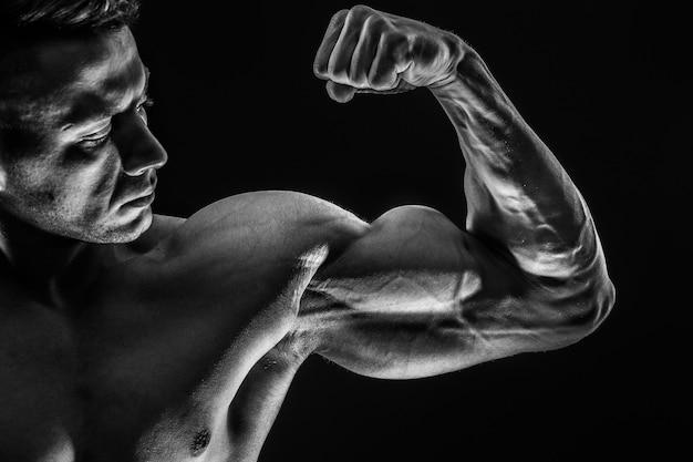 Sterke atletische sexy gespierde man op zwarte ruimte met biceps