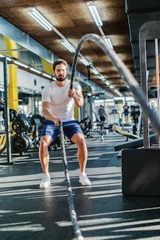 Sterke bebaarde ernstige blanke man doet oefeningen met touwen vechten. gym interieur.