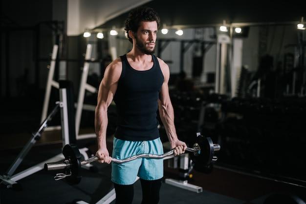 Sterke, bebaarde jonge man met gespierd, stug lichaam in sportkleding die traint met barbell