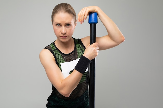 Sterke blonde meisje in sportkleding houdt zich bezig met fitness op een grijze achtergrond