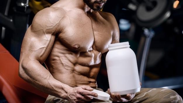 Sterke bodybuilder atletische fitness man oppompen abs spieren training bodybuilding concept