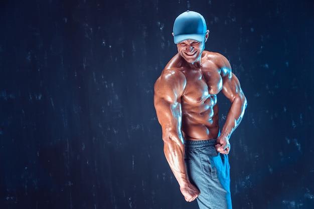 Sterke bodybuilder die honkbalpet draagt