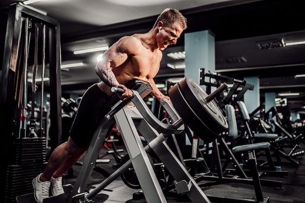 Sterke bodybuilder die zwaargewicht oefening voor terug op machine doet. t-pull oefening