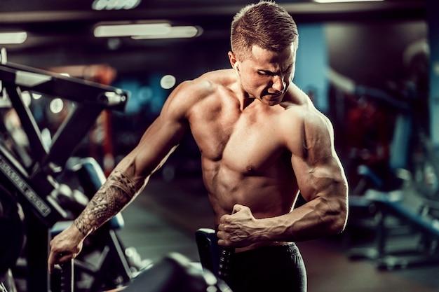 Sterke bodybuilder die zwaargewicht oefening voor terug op machine doet