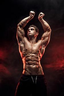 Sterke bodybuilder man met perfecte buikspieren, schouders, biceps, triceps, borst poseren in rook handen omhoog.