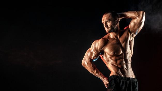 Sterke bodybuilder man met perfecte buikspieren, schouders, biceps, triceps, borst.
