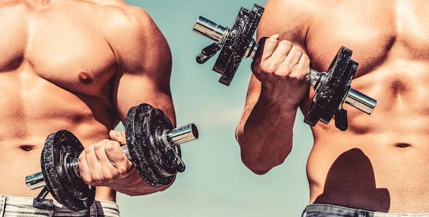 Sterke bodybuilder, perfecte deltaspieren, schouders, biceps, triceps en borst. halter. gespierde bodybuilder jongens, oefeningen met halters. spieren met halter. man trainen met halters