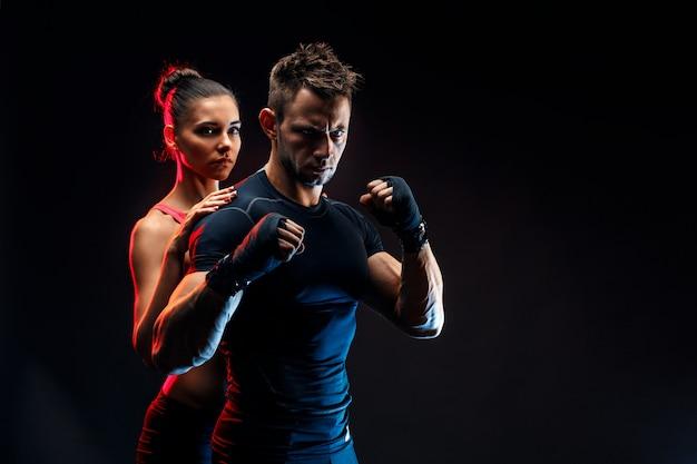 Sterke bokser in houding met handwraps op zijn vuisten met vriendin achter hem.