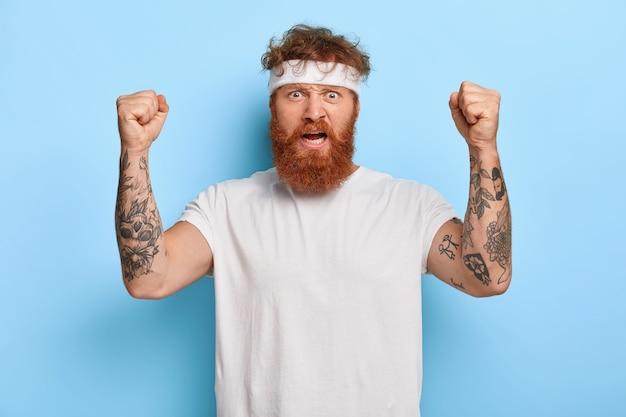 Sterke boze sportman met rood haar, heft getatoeëerde armen op