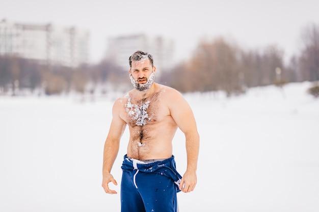 Sterke brute naakte man met baard in de sneeuw buiten poseren