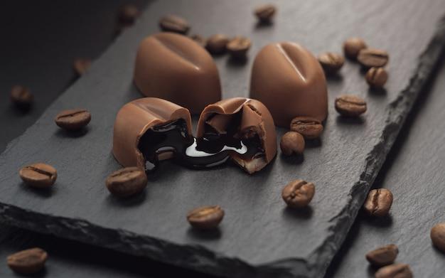Sterke drank lekte uit gebroken stuk chocolade met koffiebonen op zwarte stenen plaat