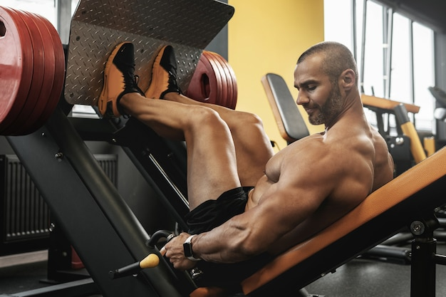 Sterke en gespierde bodybuilder die een zittende beenpersoefening doet in een sportschool