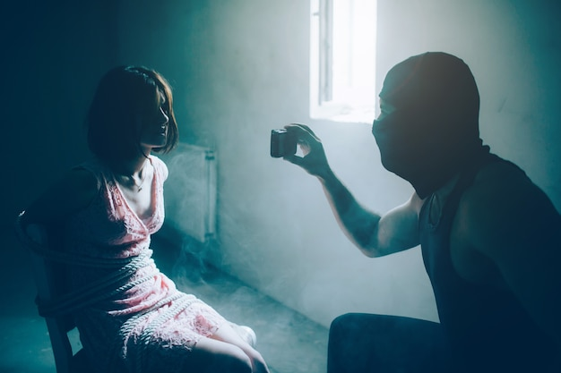 Sterke en gespierde man in zwart masker houdt telefoon voor meisje en kijkt naar haar.