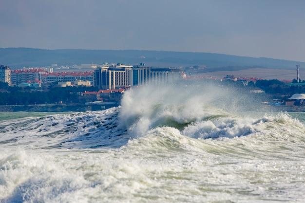 Sterke en gevaarlijke storm in de zwarte zee. mooie en grote stormgolf in gelendzhik bay bij de badplaats gelendzhik, aan het water en de vuurtoren.