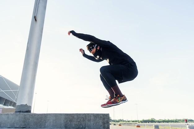 Sterke en knappe gezonde bebaarde man die plyometrische sprongoefening doet in crossfit-training buitenshuis