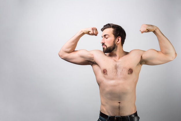 Sterke en krachtige man zonder shirt staat op witte muur en poseren. hij laat zijn grote spieren zien en hoeveel kracht hij heeft. hij houdt van zichzelf. weergave knippen.