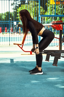 Sterke en sexy sportieve vrouw die buiten op de grond traint