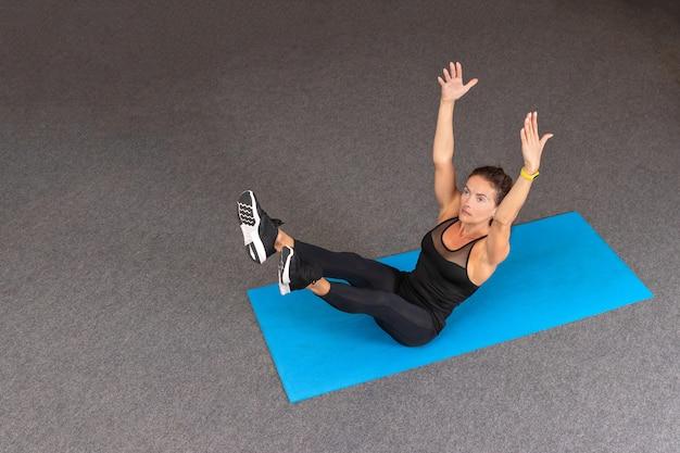 Sterke en sportieve fitness vrouw in zwarte sportkleding doen oefeningen op sportschool