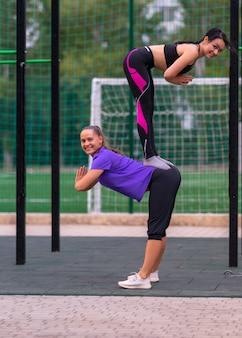 Sterke fit jonge vrouwen die acrobatische yoga doen