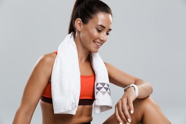 Sterke gelukkige vrolijke jonge sportvrouw poseren geïsoleerd binnenshuis met handdoek kijken naar horloge.