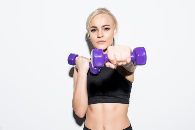 Sterke gespierde blonde meisje kickjob met blauwe halters op wit