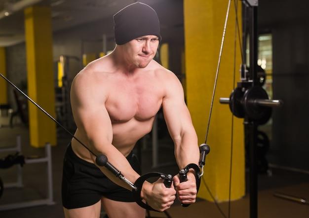 Sterke gespierde bodybuilder doen oefening op bars in de sportschool. een deel van het fitnesslichaam. sport en fitness. fitness man in de sportschool. fitness training