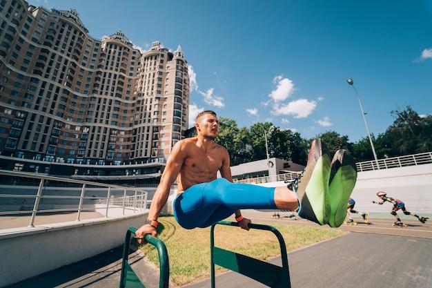 Sterke gespierde man doet oefeningen op ongelijke staven in straatgymnastiek buiten. workout levensstijl concept.