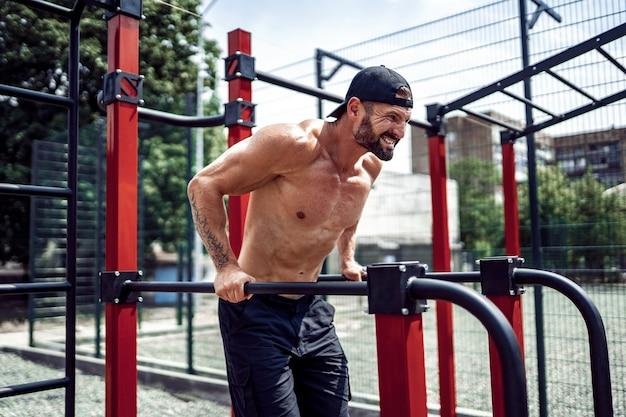 Sterke gespierde man doet push-ups op ongelijke bars in de straat street gym