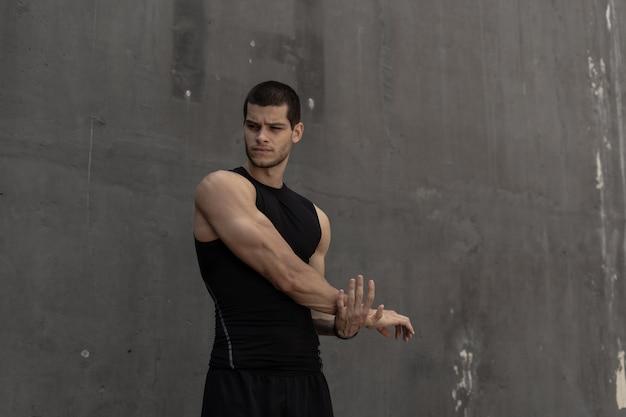 Sterke gespierde, sportieve man die opwarmt, zich klaar maakt voor traini