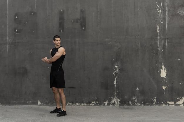 Sterke gespierde, sportieve man die opwarmt, zich klaarmaakt voor training