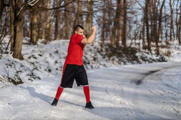Sterke gespierde vechter sparren in de natuur op besneeuwde winterdag. boksen, winterfitness