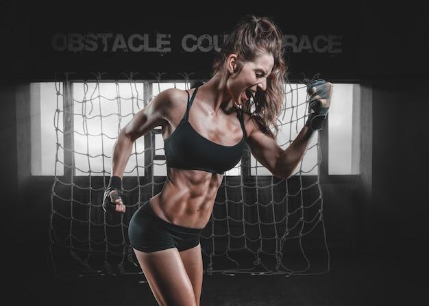 Sterke gespierde vrouw buigt haar biceps na de training.