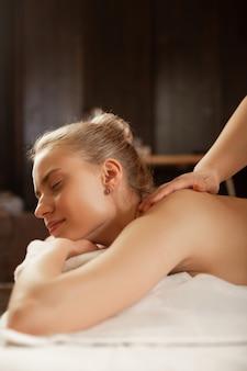 Sterke handen. rustige blonde dame die spa-complex bezoekt en massage krijgt van ervaren meester